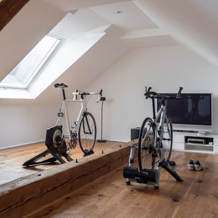 Multifunktionaler, Mittelgroßer Moderner Fitnessraum mit weißer Wandfarbe, braunem Holzboden, braunem Boden und gewölbter Decke in Dortmund