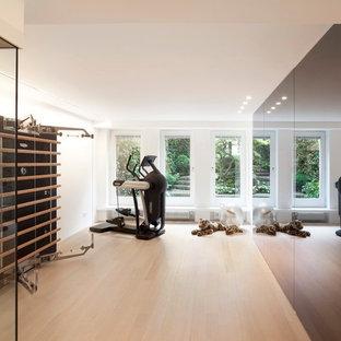 Multifunktionaler Moderner Fitnessraum mit weißer Wandfarbe und hellem Holzboden in Köln