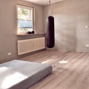 Multifunktionaler, Mittelgroßer Industrial Fitnessraum mit grauer Wandfarbe, Laminat, grauem Boden und Tapetendecke in Sonstige