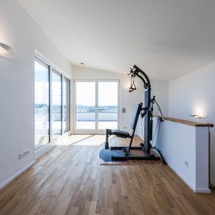 Multifunktionaler, Mittelgroßer Moderner Fitnessraum mit weißer Wandfarbe und braunem Holzboden in Sonstige