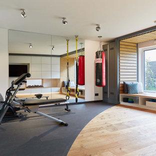 Exempel på ett stort modernt hemmagym med grovkök, med vita väggar, mellanmörkt trägolv och brunt golv
