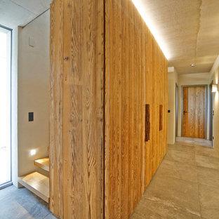 Modern inredning av en mellanstor hall, med grå väggar, klinkergolv i keramik och grått golv
