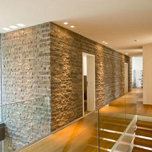 Modern inredning av en stor hall, med vita väggar och mellanmörkt trägolv