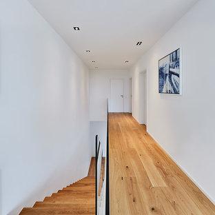 Großer Nordischer Flur mit weißer Wandfarbe, braunem Holzboden und braunem Boden in Düsseldorf
