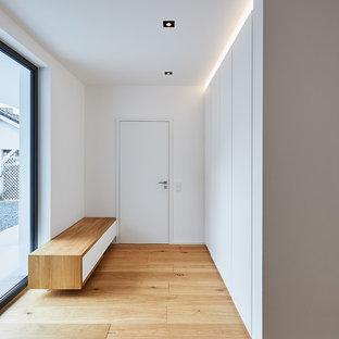 Mittelgroßer Moderner Flur mit weißer Wandfarbe, braunem Holzboden und braunem Boden in Düsseldorf