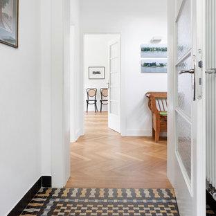 Aménagement d'un couloir scandinave de taille moyenne avec un mur blanc et un sol en carrelage de céramique.