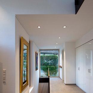 На фото: коридор среднего размера в современном стиле с белыми стенами, бетонным полом и серым полом с