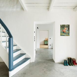Exemple d'un petit couloir nature avec un mur blanc, béton au sol et un sol gris.