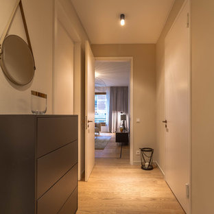 Mittelgroßer Moderner Flur mit weißer Wandfarbe, hellem Holzboden und beigem Boden in Berlin