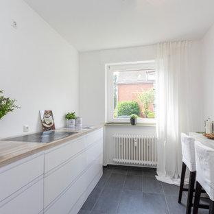 エッセンの小さい北欧スタイルのおしゃれな廊下 (白い壁、ラミネートの床、グレーの床、折り上げ天井) の写真