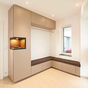 Idéer för en liten modern hall, med vita väggar och beiget golv