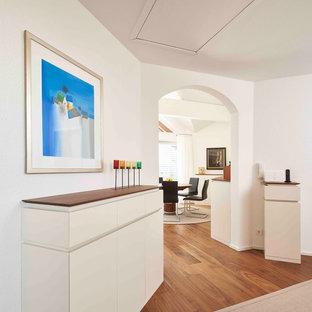 Moderner Flur mit weißer Wandfarbe, braunem Holzboden und braunem Boden in Stuttgart