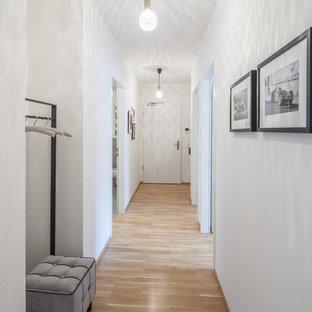 Свежая идея для дизайна: маленький коридор в стиле модернизм с белыми стенами, полом из ламината и коричневым полом - отличное фото интерьера