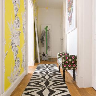 Bild på en liten eklektisk hall, med gula väggar, mellanmörkt trägolv och brunt golv