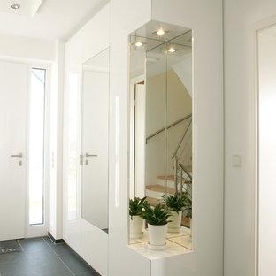 他の地域の中サイズのコンテンポラリースタイルのおしゃれな廊下 (白い壁、ラミネートの床、黒い床) の写真