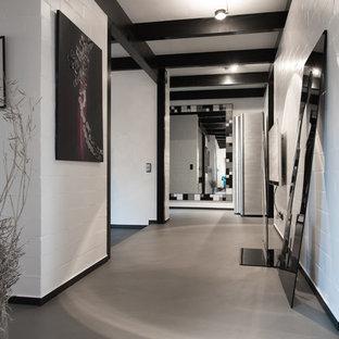 Großer Moderner Flur mit weißer Wandfarbe, Betonboden und grauem Boden in Köln
