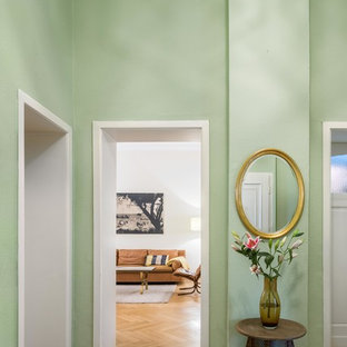 Mid-sized midcentury hallway in Cologne with green walls, light hardwood floors and brown floor.