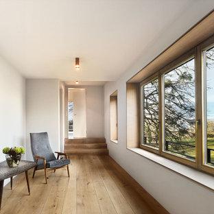 Großer Moderner Flur mit weißer Wandfarbe, braunem Holzboden und braunem Boden in München