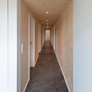 На фото: большой коридор в скандинавском стиле с коричневыми стенами, полом из терраццо и черным полом с