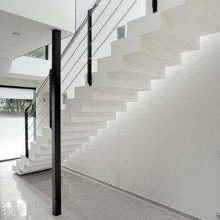 Idées déco pour un très grand couloir moderne avec un mur blanc, un sol en carrelage de porcelaine et un sol blanc.