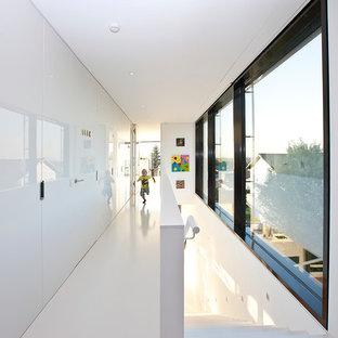 Foto på en stor funkis hall, med vita väggar och linoleumgolv