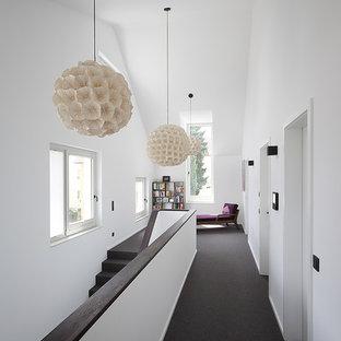Mittelgroßer Moderner Flur mit weißer Wandfarbe, Teppichboden und schwarzem Boden in Stuttgart
