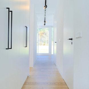 Modelo de recibidores y pasillos minimalistas, de tamaño medio, con paredes blancas y suelo de madera clara