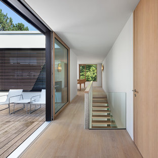 Mittelgroßer Moderner Flur mit weißer Wandfarbe und braunem Holzboden in München