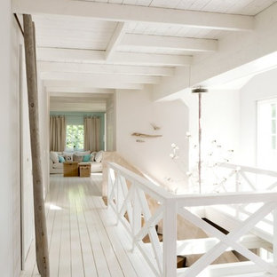 Inspiration for a large beach style hallway in Hamburg with white walls and painted wood floors.