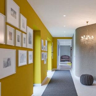 Cette photo montre un couloir éclectique de taille moyenne avec un mur jaune et un sol gris.