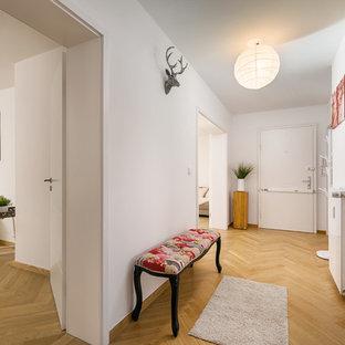Kleiner Moderner Flur mit weißer Wandfarbe, braunem Holzboden und braunem Boden in München