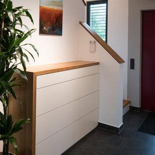 Idéer för att renovera en liten funkis hall, med vita väggar, skiffergolv och svart golv