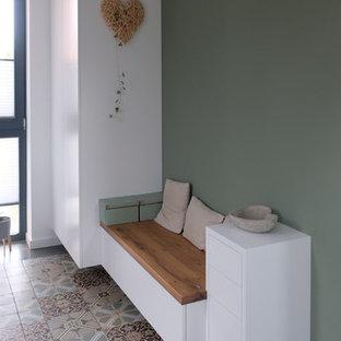 Exempel på en mellanstor modern hall, med gröna väggar och klinkergolv i keramik
