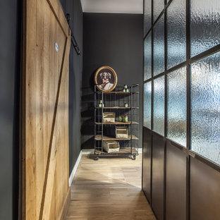 Kleiner Industrial Flur mit schwarzer Wandfarbe, braunem Holzboden und braunem Boden in Berlin