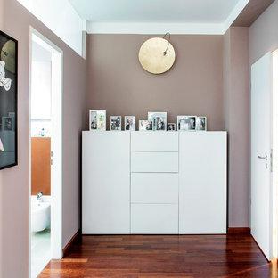 Inspiration pour un couloir design de taille moyenne avec un mur violet et un sol en bois brun.