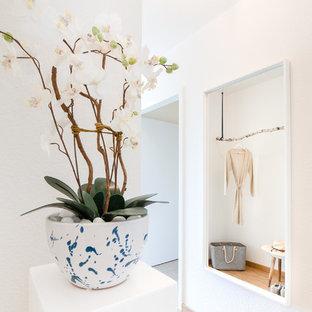 Inspiration pour un petit couloir nordique avec un mur blanc, un sol en bambou et un sol beige.