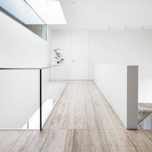 Diseño de recibidores y pasillos minimalistas, de tamaño medio, con paredes blancas y suelo de travertino