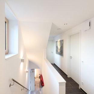 Kleiner Moderner Flur mit weißer Wandfarbe und schwarzem Boden in Sonstige