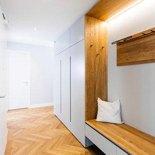 На фото: коридор среднего размера в скандинавском стиле с паркетным полом среднего тона, коричневым полом и серыми стенами с