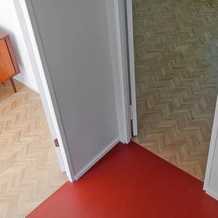 Cette image montre un couloir minimaliste avec un sol en linoléum, un mur blanc et un sol rouge.