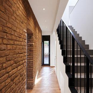 Idee per un ingresso o corridoio industriale di medie dimensioni con pareti bianche, pavimento in legno massello medio e pavimento marrone