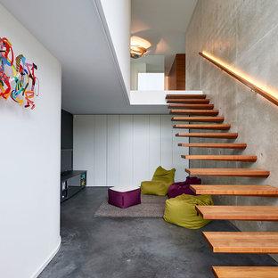Großer Moderner Flur mit weißer Wandfarbe, Betonboden und schwarzem Boden