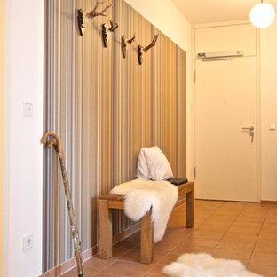 Idée de décoration pour un grand couloir design avec un mur beige, un sol en carreau de terre cuite et un sol rouge.