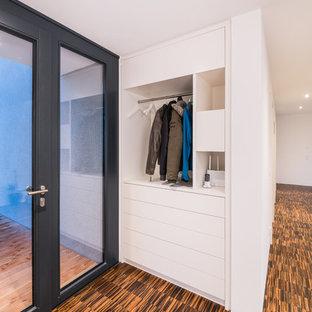 Cette image montre un couloir minimaliste de taille moyenne avec un mur blanc, un sol en bambou et un sol marron.