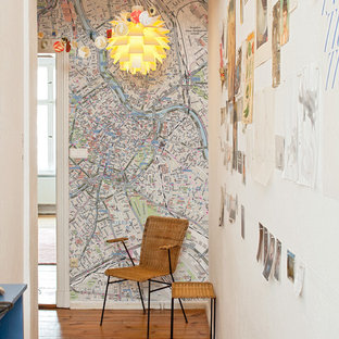 Aménagement d'un petit couloir éclectique avec un mur multicolore et un sol en bois brun.