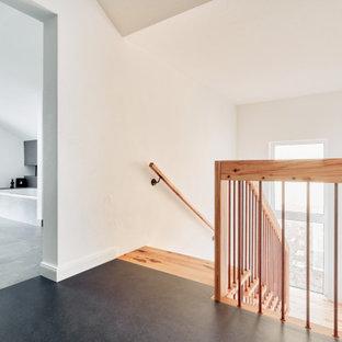 Cette image montre un couloir urbain de taille moyenne avec un mur blanc, un sol en linoléum et un sol gris.