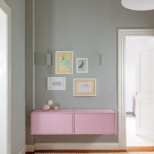 Kleiner Moderner Flur mit grauer Wandfarbe, braunem Holzboden und weißem Boden in Stuttgart