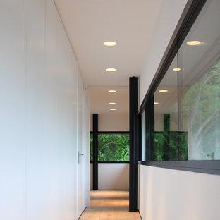 Mittelgroßer Industrial Flur mit weißer Wandfarbe, hellem Holzboden und beigem Boden in Hannover
