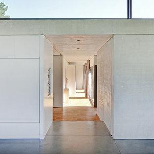 Großer Moderner Flur mit grauer Wandfarbe und Betonboden in Stuttgart