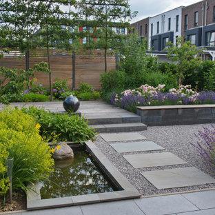 Moderner Kiesgarten mit Blumenbeet und direkter Sonneneinstrahlung in Hamburg